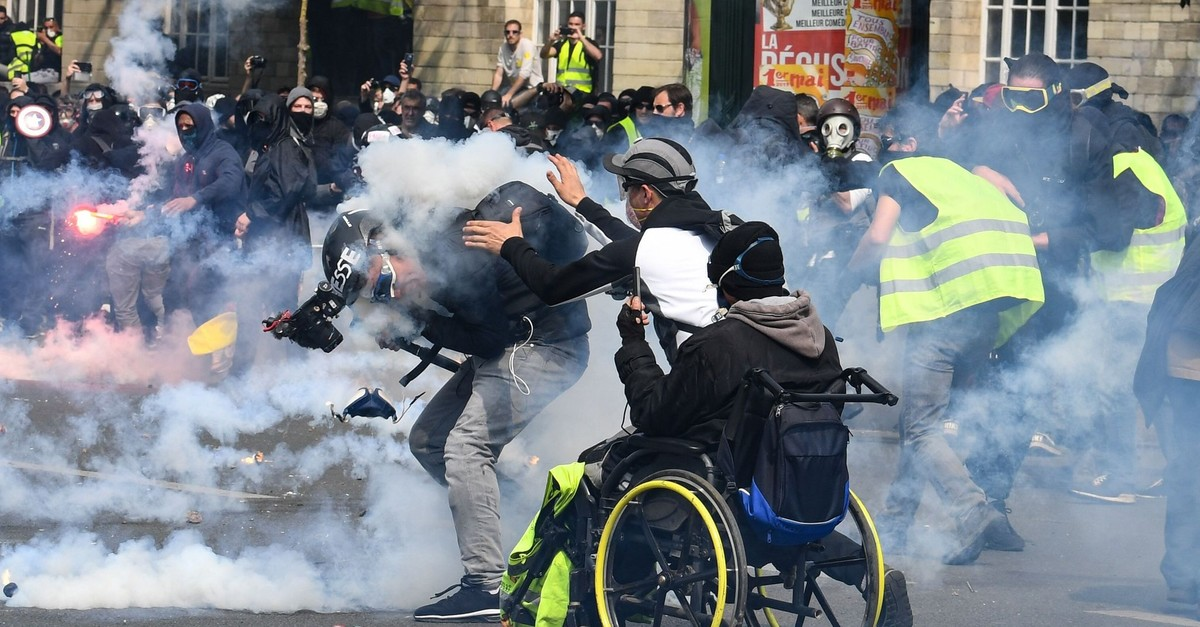 A cameraman reacts as he is hit by a tear gas canister as a u201cyellow vestu201d protester goes to help him during clashes with police in Paris, May 1, 2019.