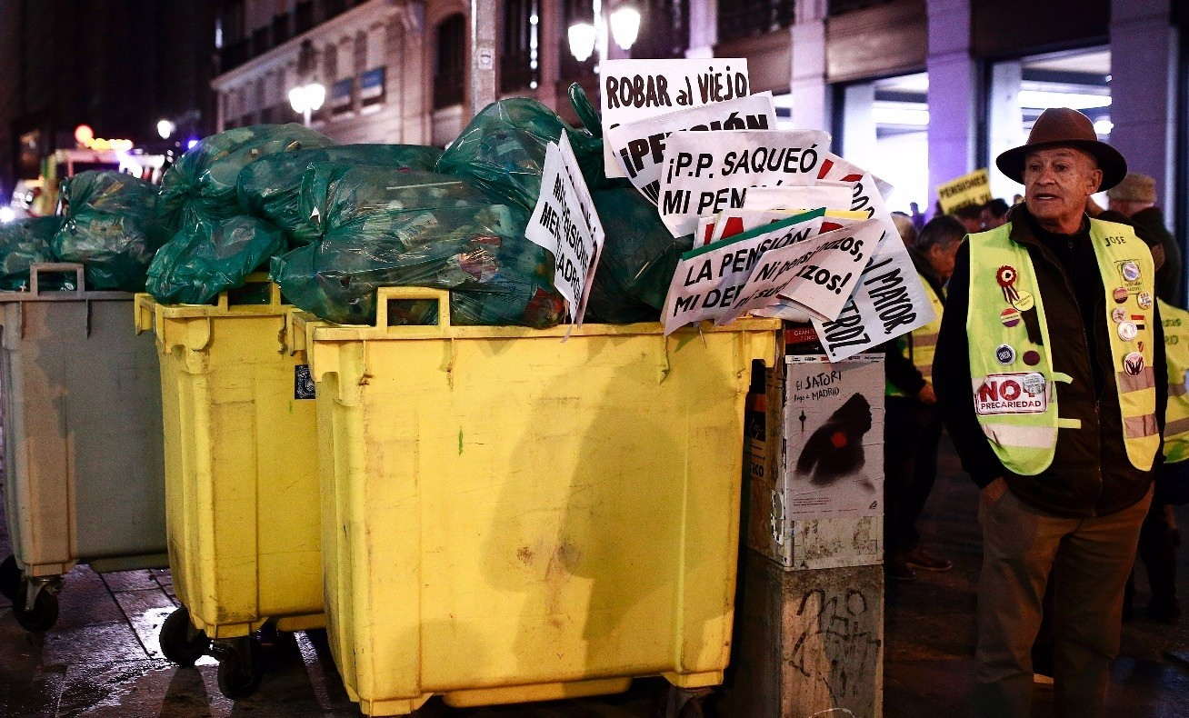 A protester wearing a yellow vest stands next to a trash container filled with placards used during a demonstration, Madrid, Dec. 15.