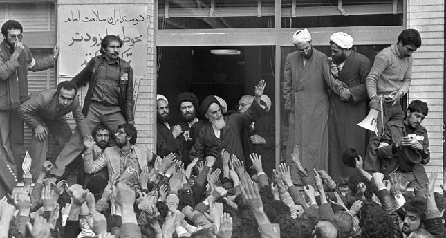 In this Feb. 1, 1979 file photo, Ayatollah Ruhollah Khomeini, center, waves to followers as he appears on the balcony of his headquarters in Tehran, Iran.
