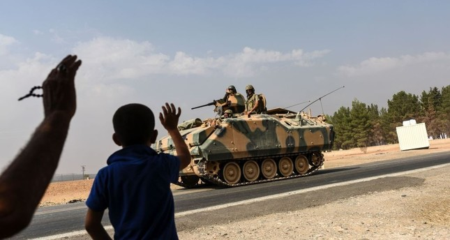 A boy waving to Turkish tank convoy driving into Syria from the Karkamış distrcit in Turkey's southern province of Gaziantep on the border wtih Syria, on Aug. 26.