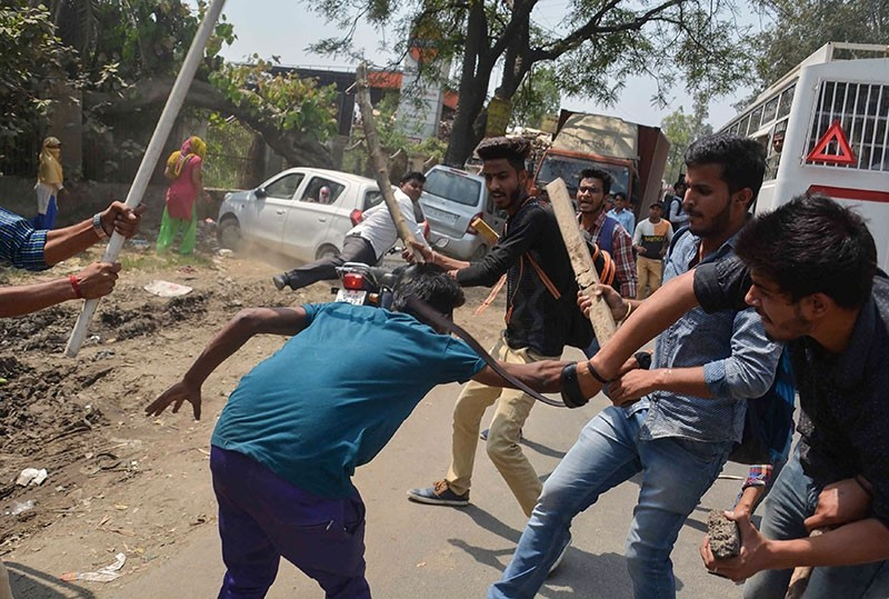A protester (C) is beaten by Indian students after members of the Dalit community and other ,low caste, groups threw bricks at their college during countrywide protests, in Meerut in Uttar Pradesh state on April 2, 2018.