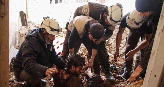 Members of the Syrian civil defense volunteers, also known as the White Helmets, remove a victim from the rubble of his house on April 8, 2017, following a reported air strike by regime forces in the southern Syrian city of Daraa. (AFP Photo)