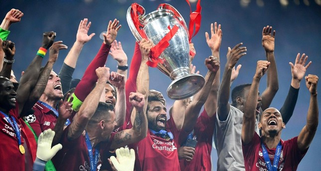 Liverpool's Egyptian forward Mohamed Salah (C) raises the European Champion Clubs' Cup as he celebrates with teammates (AFP Photo)