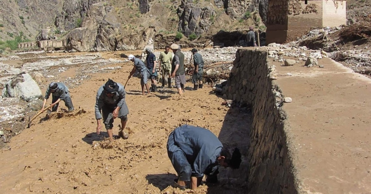 This May 22, 2019 handout photo shows men working at a site near the Minaret of Jam following floodwaters in the Shahrak District of Ghor Province, Afghanistan. (AFP Photo/Information and Culture Department of Ghor)