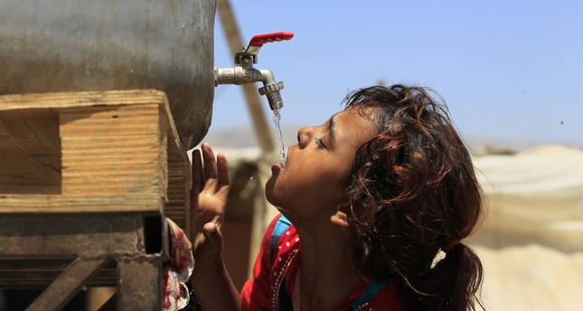 Syrian refugee Amani al-Antar, 7, who fled with her family from the city of Deir al-Zour, Syria, drinking water at a Syrian refugee camp in the eastern Lebanese town of Saadnayel, Bekaa Valley.