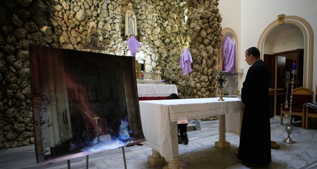 Father Gabriel Ferone stands next to a photo of Notre Dame Cathedral inside the church.