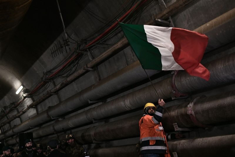 A worker puts up the Italian national flag during a visit of Italyu2019s Interior Minister and deputy Prime Minister Matteo Salvini to the building site of a high-speed train line between Italy and France, Feb. 1, 2019 in Chiomonte, Italy. (AFP Photo)