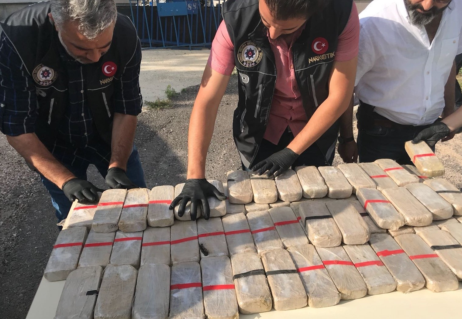 Narcotics police in the central city of Niu011fde examine packs of heroin smuggled inside a hidden compartment of a car on June 21.