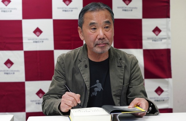 Japanese novelist Haruki Murakami autographs his novel Killing Commendatore during a press conference at Waseda University.