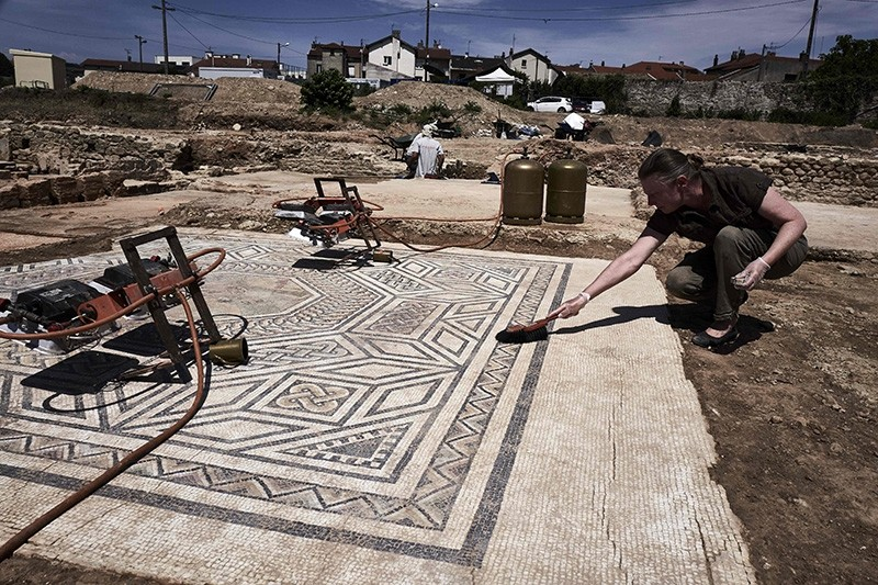 An archaeologist works on a mosaic on July 31, 2017, on the archaeological antiquity site of Sainte-Colombe, near Vienne, eastern France (AFP Photo)