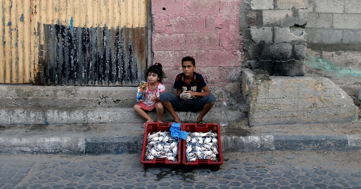 A Palestinian boy sits next to his sister, Gaza City, Sept. 16, 2019.