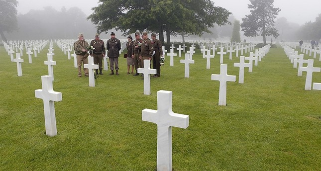 French members of WWII veteran association Les Fleurs de la Memoire, Flowers for Memory, pay their respects in front of the tomb of Morris H. Hilghman Jr of the PVT 507 Parachute Inf Regiment from WV, who died on June 9, 1944. (AP Photo)