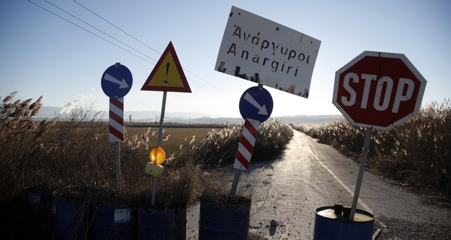 Signs close off a road damaged in a landslide in the village of Anargyri near the town of Amynatio, northern Greece.