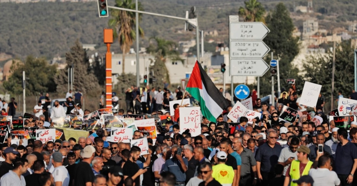 Arab Israeli protesters carry placards and chant slogans as they block a highway near the Arab Israeli city of Ar'Ara, north of Israel during a demonstration against violence, organised crime and recent killings among their communities, on October 13