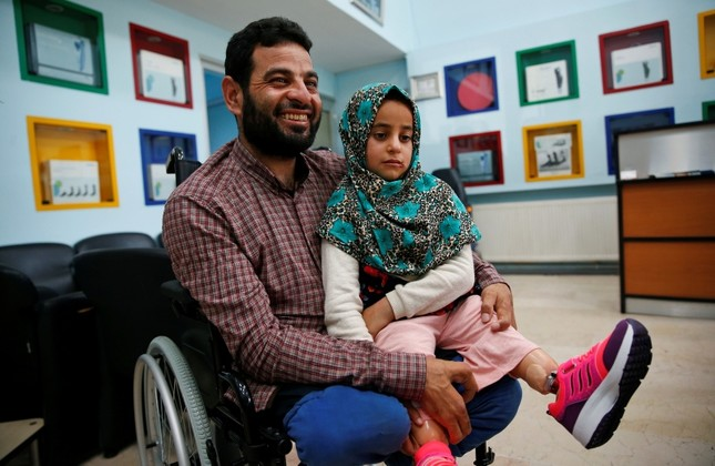 In this Thursday, July 5, 2018 photo, Maya Meri sits on her father Mohammed's lap after being fitted with prosthetic legs at a rehabilitation clinic in Istanbul, Turkey. (AP Photo)