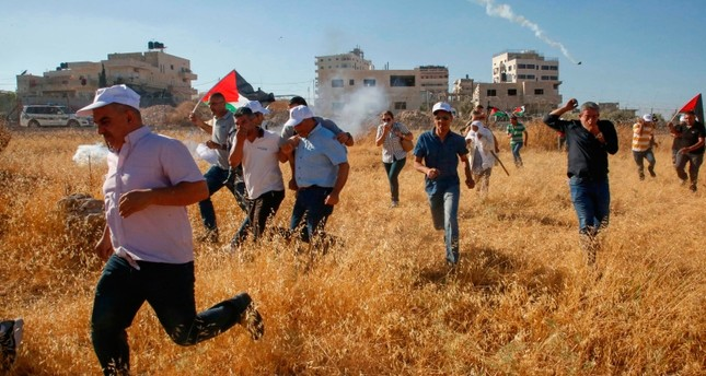 Palestinians run for cover after Israeli forces fire tear gas canisters during a demonstration against the demolishing of buildings in the Palestinian village of Beit Sahur in the occupied West Bank, July 20, 2019. (AFP Photo)