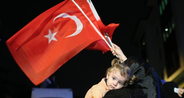 A supporter of Turkey's ruling Justice and Development Party holds a baby as she waves Turkish flags, İstanbul, Turkey, June 7, 2015.
