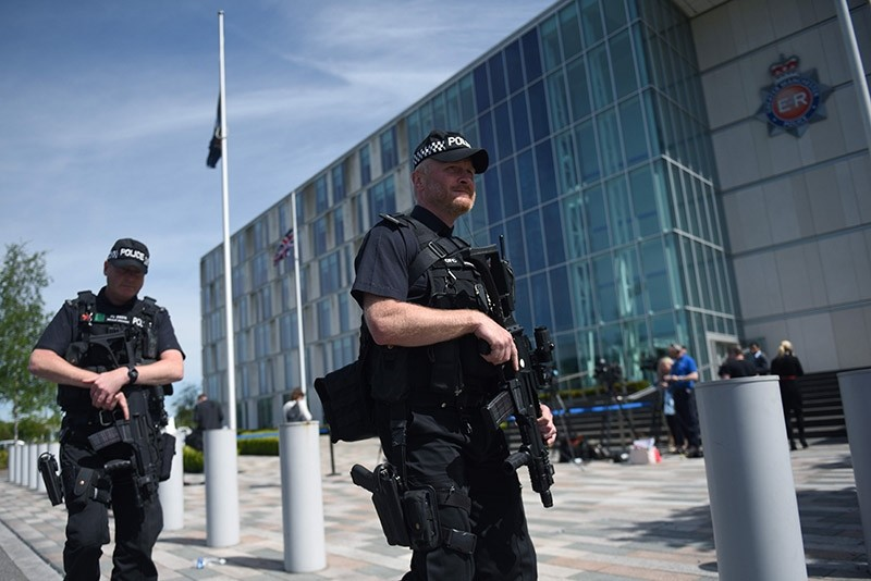 Flags fly at half-mast as armed British Police officers walk on patrol with their weapons outside of Greater Manchester Police force's headquarters in Manchester, northwest England on May 23, 2017 (AFP Photo)
