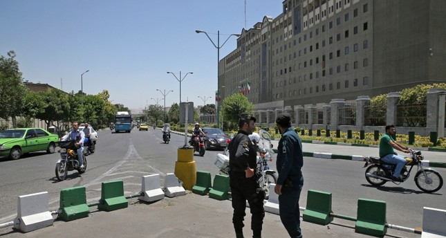 Police officers stand guard as vehicles drive past Iran's parliament building in Tehran, Iran, Thursday, May 8, 2017 (AP File Photo)