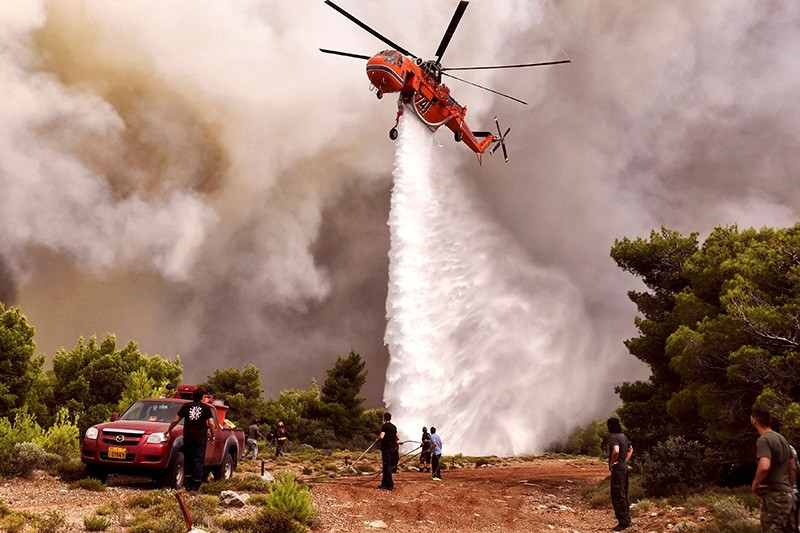 A firefighting helicopter drops water to extinguish flames during a wildfire at the village of Kineta, near Athens, on July 24, 2018.