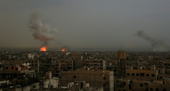 Smoke and flames rise from buildings following reported Syrian regime airstrikes on the opposition-held town of Saqba in the besieged  Damascus suburb of Eastern Ghouta, March 4.