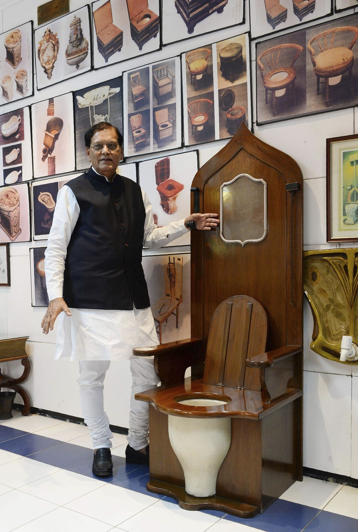 Founder of sanitation charity Sulabh International Bindeshwar Pathak speaks during an interview as he stands beside a replica of a toilet used by French King Louis XIV in New Delhi.