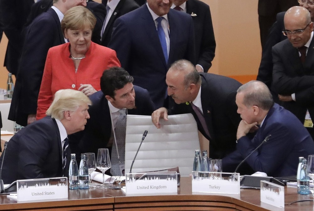 German Chancellor Angela Merkel looks on as U.S. President Donald Trump (L) talks to Foreign Minister Mevlu00fct u00c7avuu015fou011flu and President Recep Tayyip Erdou011fan (R) prior to the first working session on the first day of G-20 summit, Hamburg, July 7, 2017.