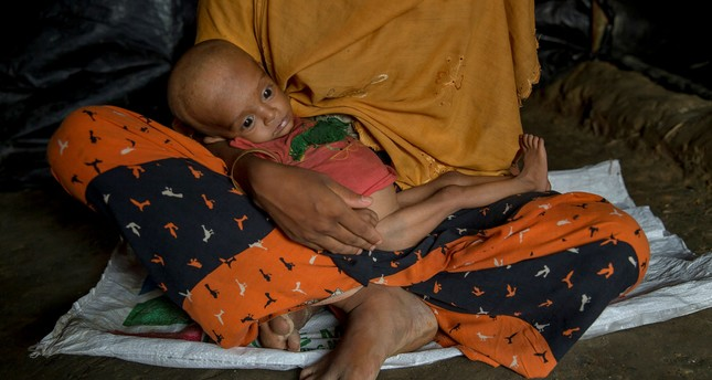 A pregnant Rohingya refugee woman holds her 10-month-old son in the Thaingkhali refugee camp, Bangladesh, Oct. 20, 2017.