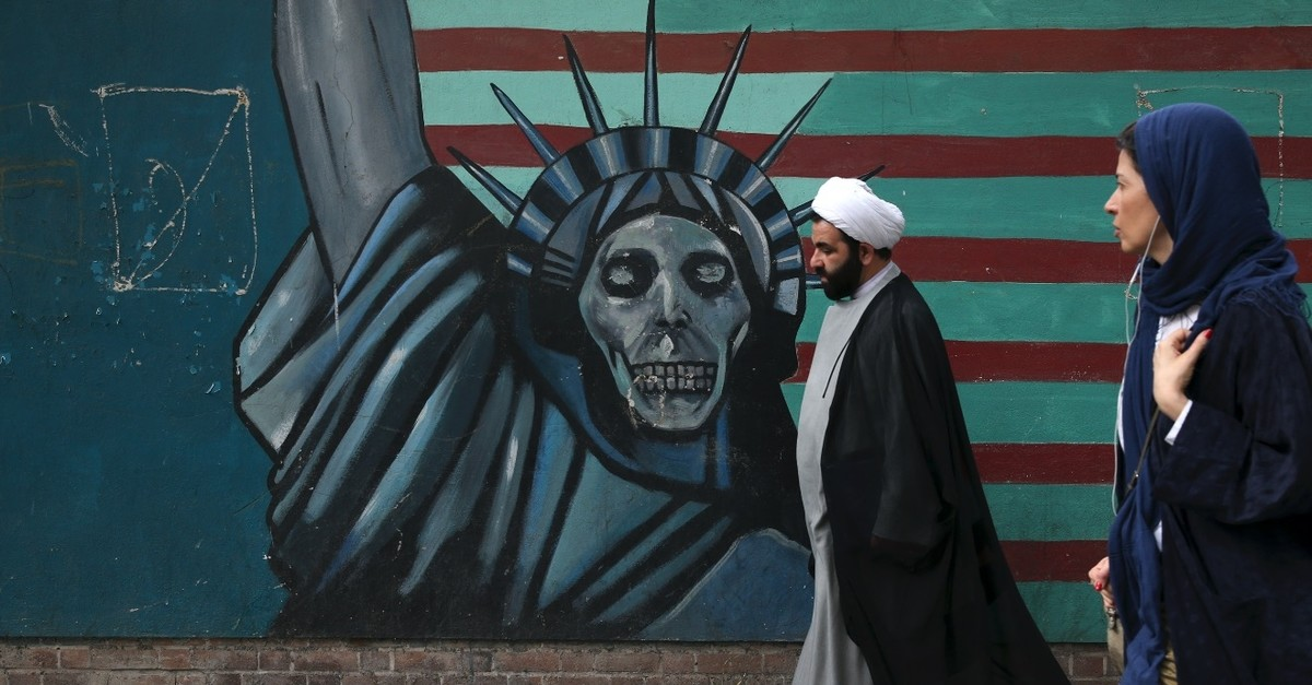 A cleric and a woman walk past an anti-U.S. mural painted on the wall of the former U.S. Embassy in Tehran, May 8, 2018.