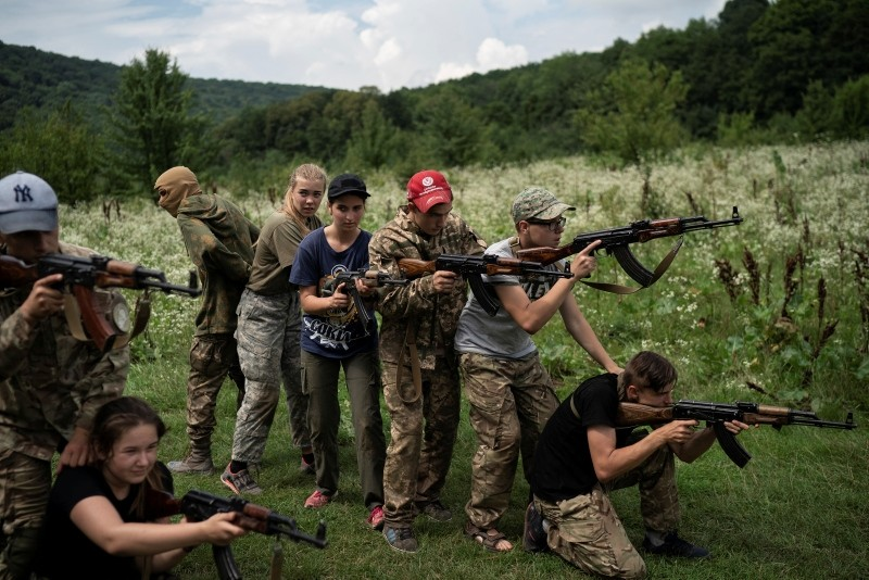 In this July 29, 2018 photo, young participants of the ,Temper of will, summer camp, organized by the nationalist Svoboda party, practice tactical formations with AK-47 assault rifles in a village near Ternopil, Ukraine. (AP Photo)