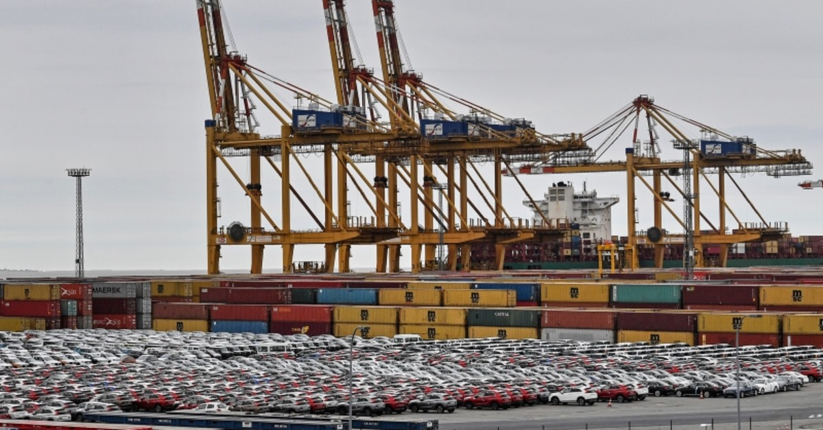 Cars for export and import are stored in front of containers on Thursday, May 16, 2019 at the harbor in Bremerhaven, Germany. (AP Photo)
