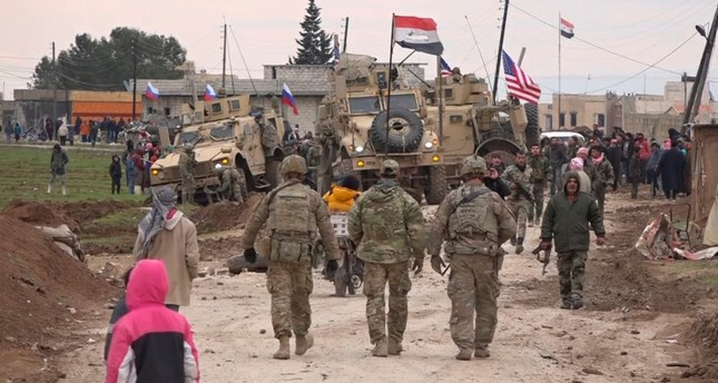 In this frame grab from video taken on Wednesday, Feb. 12, 2020, Russian, Syrian and others gather next to an American military convoy stuck in the village of Khirbet Ammo, east of Qamishli city, Syria, Wednesday, Feb. 12, 2020. AP Photo