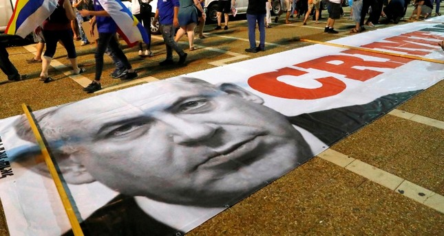 A banner with a political message and a picture of Israeli Prime Minister Benjamin Netanyahu is spread on the ground as protesters rally against the 'Jewish Nation-State Law' in Tel Aviv on August 4, 2018. (AFP Photo)