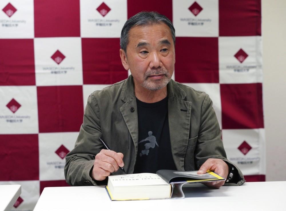 Japanese novelist Haruki Murakami autographs his novel ,Killing Commendatore, during a press conference at Waseda University.