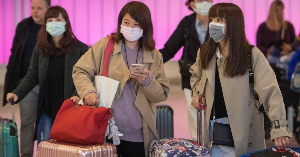 Passengers wear protective masks to protect against the spread of the coronavirus as they arrive at the Los Angeles International Airport, California, on January 22, 2020. (AFP Photo)
