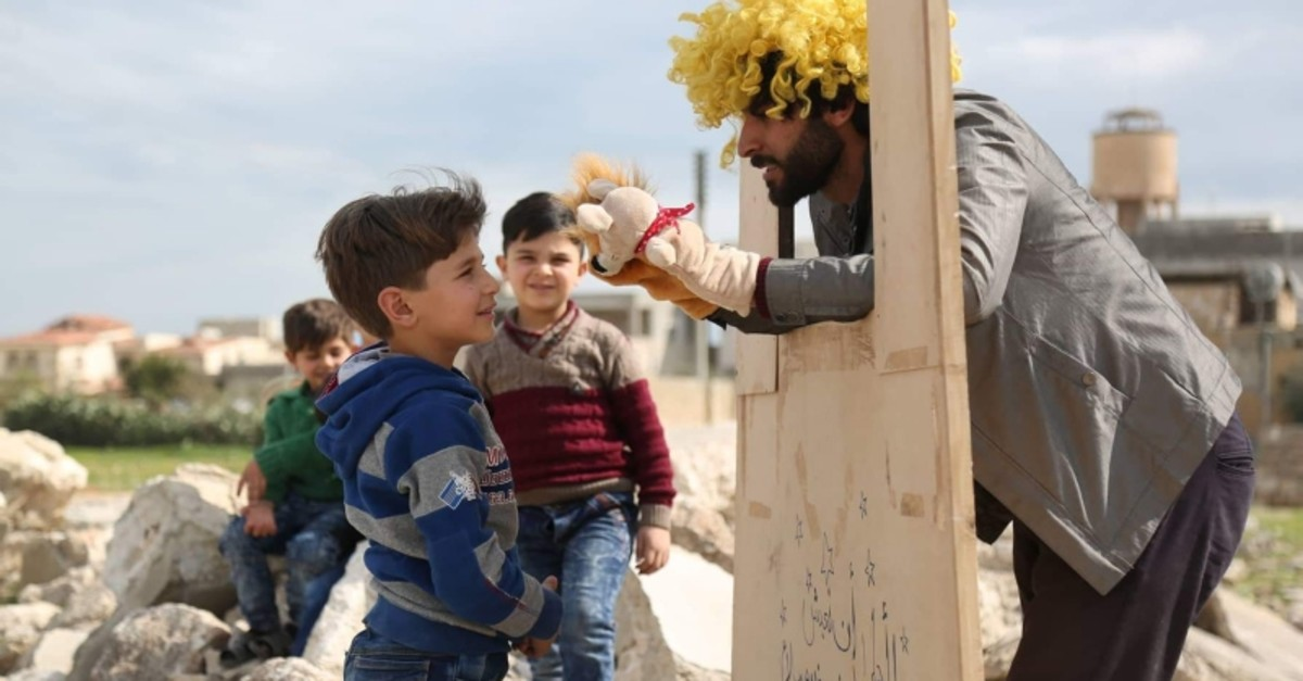 A Syrian actor holds a puppet show for children amid rubbles of buildings damaged in Assad regime attacks in Azaz, northern Syria, April 9, 2019. (AA Photo)