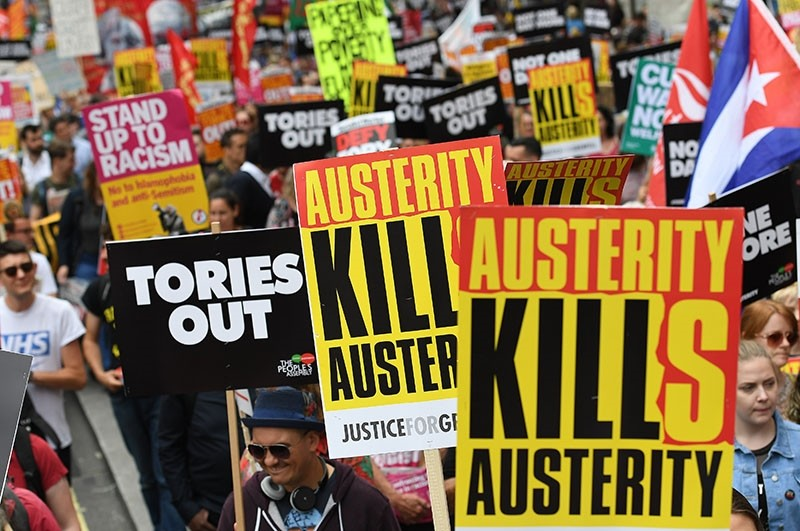 People hold placards reading 'Austerity Kills' and 'Tories out' as they take part in an anti-austerity demonstration outside Parliament in London, Britain, July 01, 2017. (EPA Photo)
