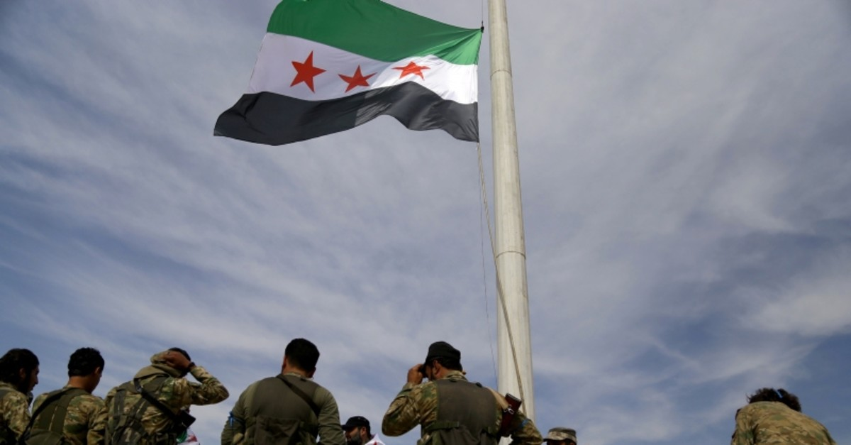Syrian National Army troops raising the Syrian flag in Tal Abyad after the city's liberation from YPG terrorists (AA Photo)
