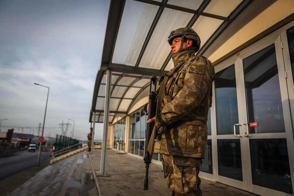 A soldier stands guard outside the courthouse in Silivri where 74 defendants stand trial on coup charges.