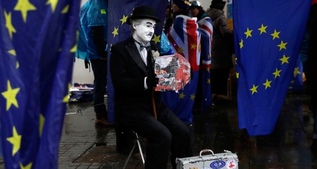 Anti-Brexit remain in the European Union supporters take part in a protest under a heavy rain outside the House of Parliament in London, Tuesday, March 12, 2019. (AP Photo)