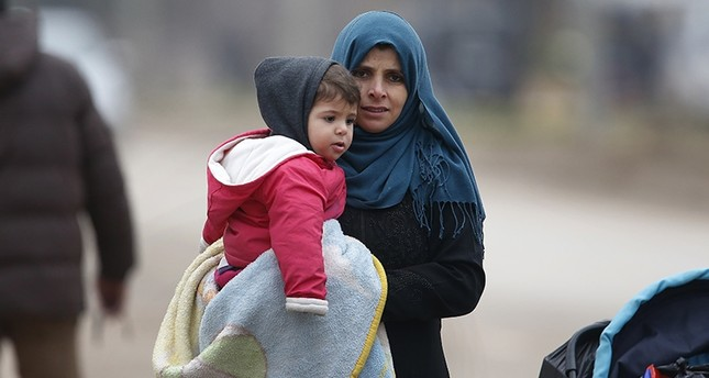 A Syrian woman holds a child and walks to Syria from Turkey at the Öncupinar border crossing with Syria, Kilis, Turkey, Jan. 26. (AP Photo)