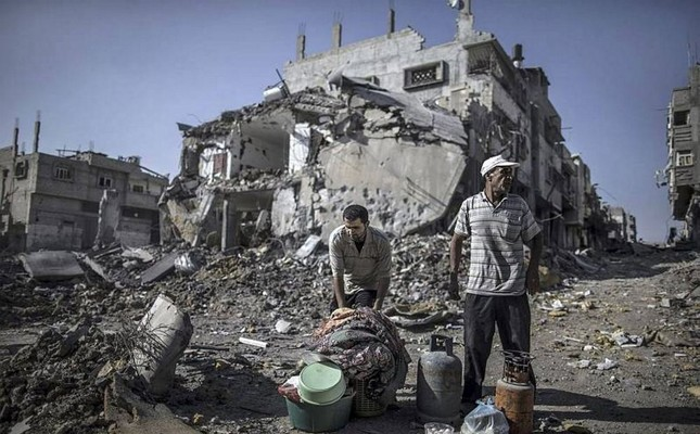Palestinian men gather things they found in the rubble of destroyed buildings in the Shejaiya residential district of Gaza City.