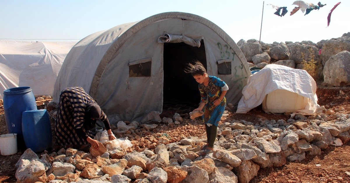 A girl who fled Idlib because of regime attacks and took refuge near the Turkish border is seen playing around her tent, Aug. 6, 2019.