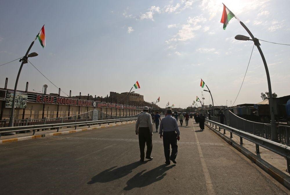 Iraqis walk down a street flying KRG flags in the Iraqi city of Kirkuk on Sept. 18.