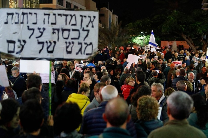 Israelis take part in a demonstration under the name ,March of Shame, to protest against government corruption and Prime Minister Benjamin Netanyahu on December 9, 2017 in Tel Aviv. (AFP Photo)