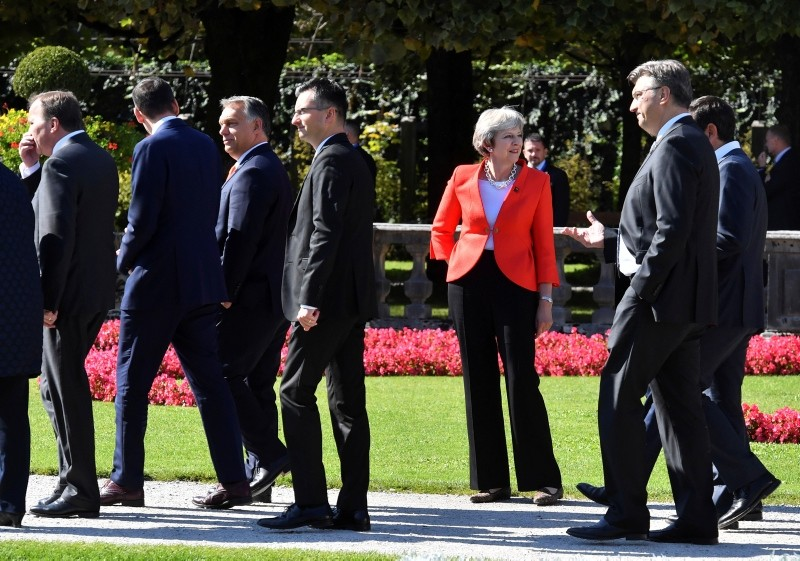 British Prime Minister Theresa May looks to passing by heads of government after the family photo at the informal EU summit in Salzburg, Austria, Thursday, Sept. 20, 2018. (AP Photo)