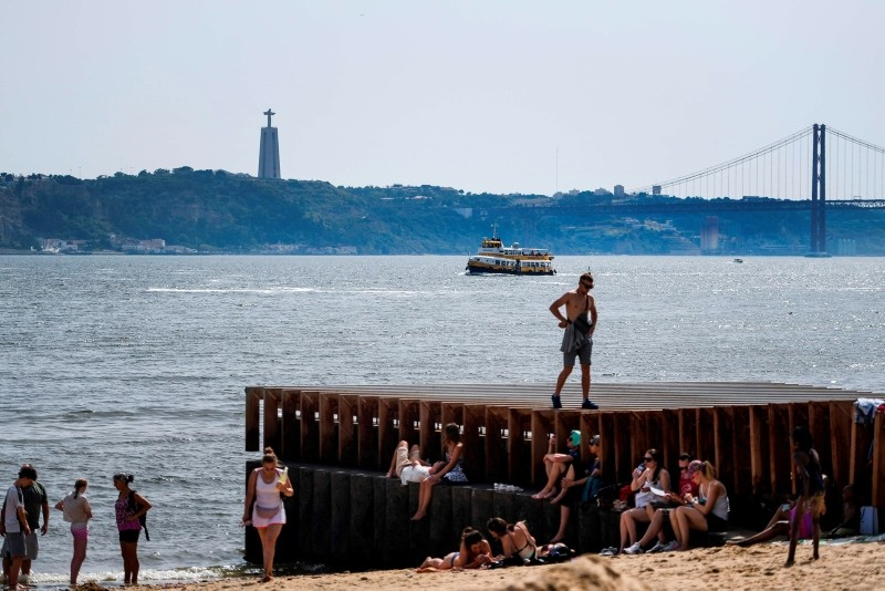 Tourists rest in the shade and cool off on a beach next to Tagus River at Ribeira das Naus in Lisbon on August 3, 2018. (AFP Photo)