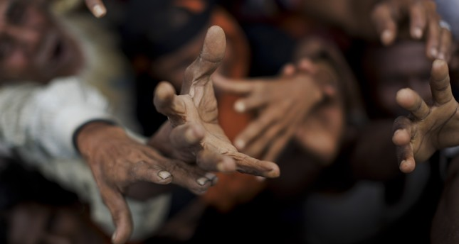 Newly arrived Rohingya stretch out their hands to receive puffed rice food rations donated by local volunteers in Kutupalong, Bangladesh, Sept. 9, 2017. (AP Photo)