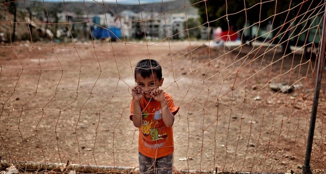 A boy looks on from behind a net at the refugee camp of Schisto, Athens, June 8, 2016.
