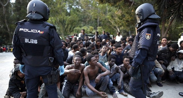 Migrants sit on the ground next to Spanish police officers after storming a fence to enter the Spanish enclave of Ceuta, Spain, Friday, Feb. 17, 2017. (AP Photo)